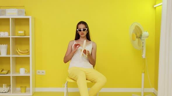 Young Woman Model Is Peeling Banana