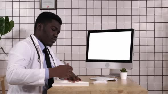 Thumbnail for Medical Doctor Taking Notes Looking Up Info on His Computer. White Display