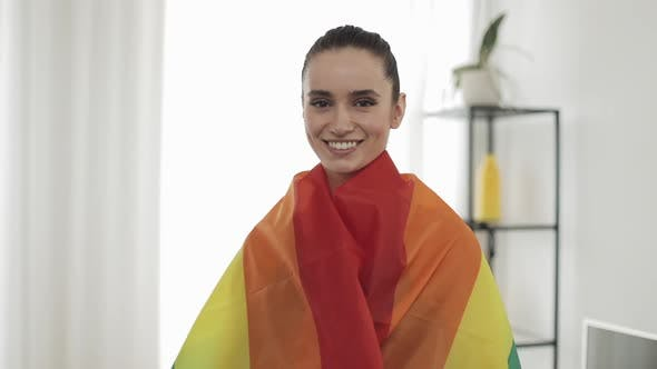 Cover Image for Portrait Young Woman Wearing LGBT Flag Standing at Home. She Looking Into the Camera, Smiling