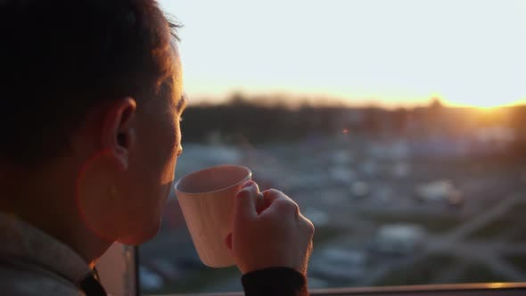 Attractive young man with a mug of hot drink admires the beautiful sunset, close-up