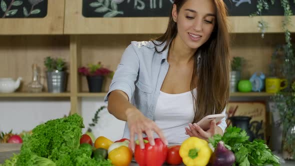 Thumbnail for Good-looking Joyful European Woman Using Her Mobile,reading Recipe and Checking Vegetables Standing
