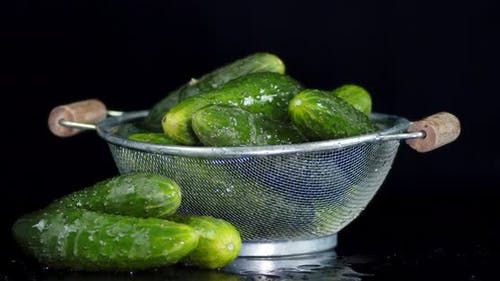 Fresh Crunchy Cucumbers in a Colander Slowly Rotate