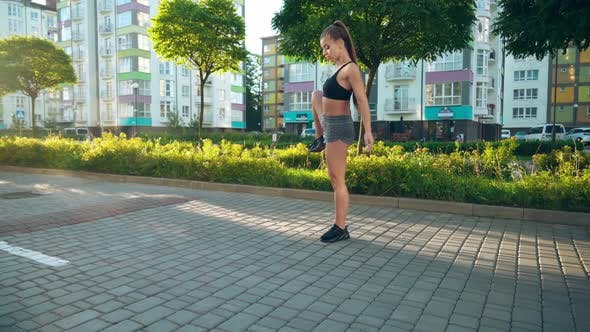 Young Woman Stretching Legs Near Multistorey Buildings.