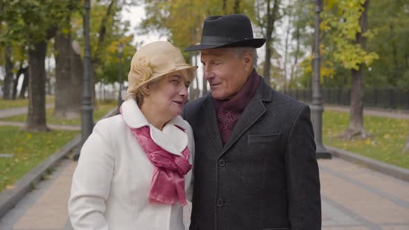 Thumbnail for Mature Caucasian Couple in Elegant Clothes Standing in the Autumn Park and Talking