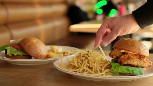 Man's hand was eating French fried, with hamburgers. Eating junk food or fast food for lunch
