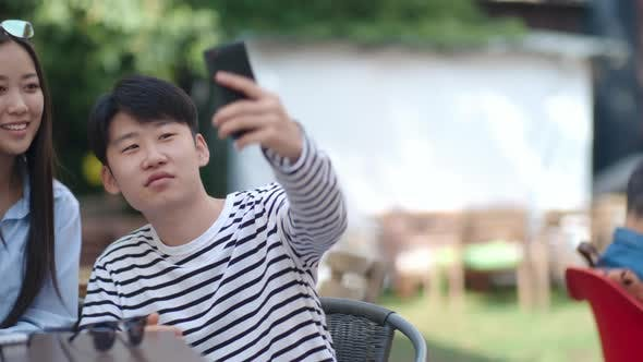 Cover Image for Asian Teenagers Taking Selfie in Outdoor Cafe