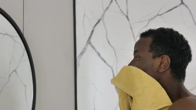 AfricanAmerican Guy Wipes Face Near Mirror in Bathroom