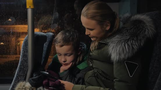 Kid with Mother Using Cellphone in the Bus