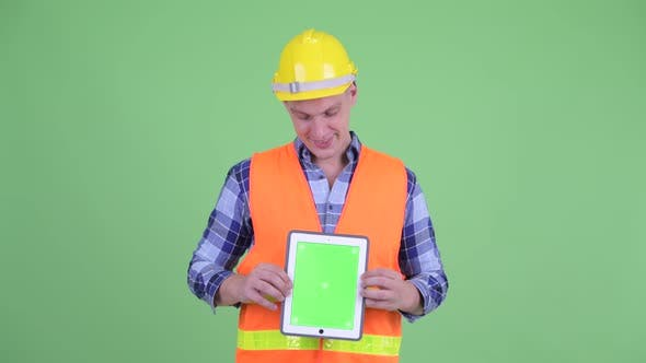 Thumbnail for Happy Young Man Construction Worker Thinking While Showing Digital Tablet