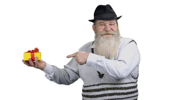 Positive Senior Man Pointing at Gift Box