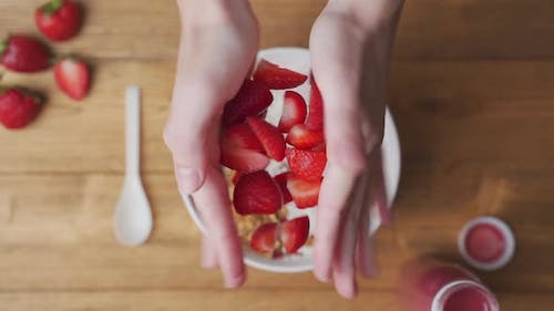 Strawberries Falling in a Bowl of Yogurt with Granola