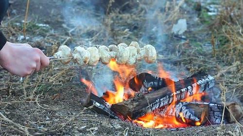 ein Mann frät und dreht sich über Champignon Steinpilze, die auf Hüte über einem offenen Feuer gepflanzt werden