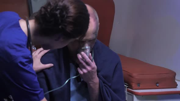Thumbnail for Sick Man Sit in Oxygen Mask in Ambulance Car.