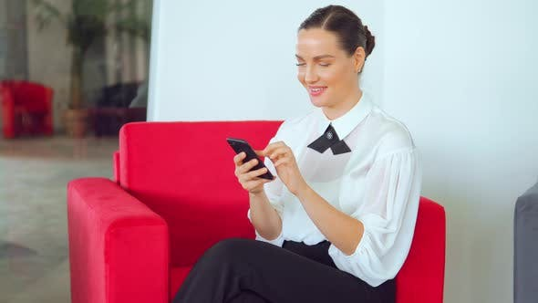 Thumbnail for Young Beautiful Woman Sitting on Armchair and Typing in Her Phone