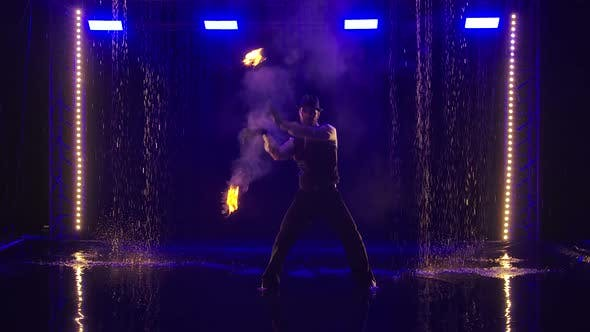 Male Artist Performing Fire Show in Slow Motion at Night. Fireshow in in a Dark Studio Under