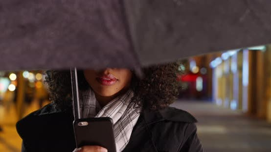 Thumbnail for Close up of woman text messaging on smartphone under umbrella on street at night