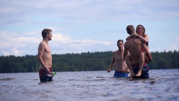 Thumbnail for Young adults swimming, bathing and playing in a shallow lake.