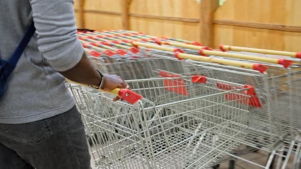 Thumbnail for Supermarket: Man Pushing Shopping Cart Through Fresh Produce Section of the Store.
