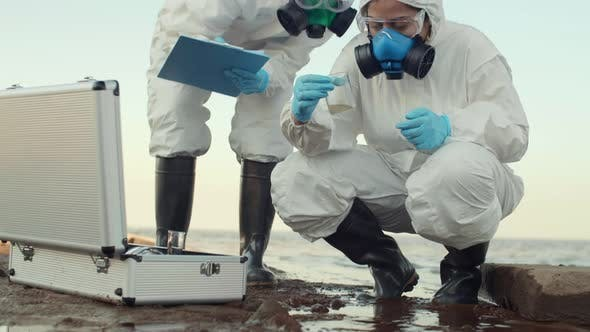 Two Ecologists Analyzing Water of Polluted Ocean
