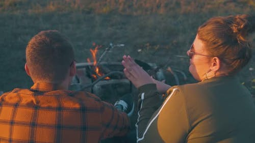 Plump Girl Tells Story to Friends at Bonfire in Evening