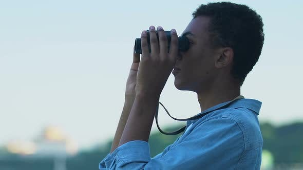 African-American male tourist observing landscape with binoculars