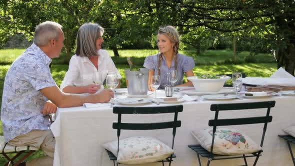 Thumbnail for WS, Family in garden together around table for dinner