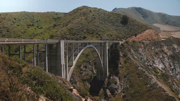Thumbnail for Scenic Wide Background Shot of Cars Moving Through Iconic Bixby Creek Bridge Over Highway 1