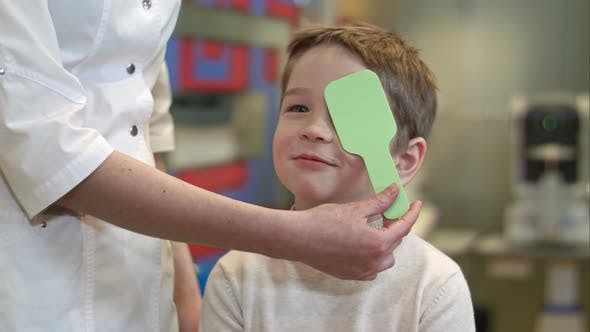 Thumbnail for Boy Looking at Vision Test with One Eye Covered with Occluder