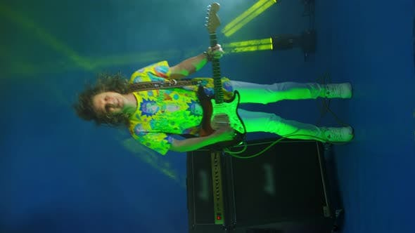 Vertical Video of a Crazy Jumping Rock Guitarist with a Guitar in His Hands on a Colored Neon