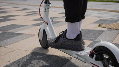 Men's Feet in Sneakers on an Electric Scooter