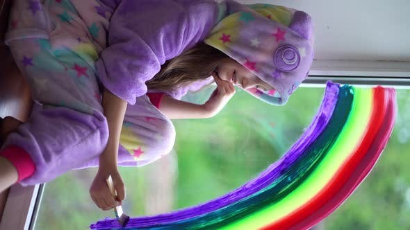 Vertical Video. School Girl in Pajamas Draws the Rainbow on the Window at Home. Stay Home, Flash Mob