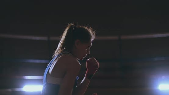 Thumbnail for Professional Beautiful Female Boxer Shoots Off Conducting a Shadow Fight in a Dark Hall Room in Slow