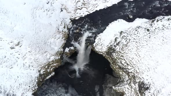 Thumbnail for AERIAL: Close Up of Waterfall in Snow, Ice Canyon in Iceland Green Grass, Cloudy