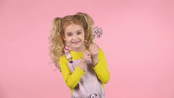 Thumbnail for Little Blond Female Is Palying with Lollipop and Smiling. Slow Motion