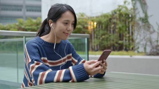 Thumbnail for Woman having voice message on cellphone at city