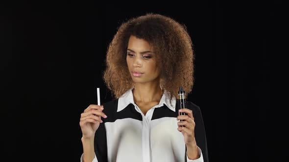 Thumbnail for Girl Makes a Choice Between an Electronic Cigarette and an Ordinary One, Black Background