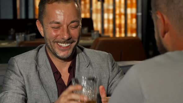 Cover Image for Cheerful Mature Man Laughing, Talking To His Friend at the Whiskey Bar