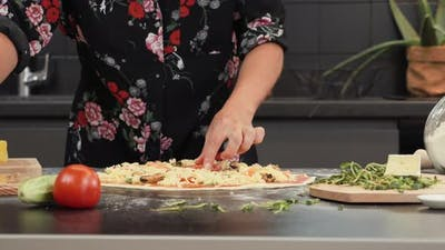 Female cooking pizza at home in modern kitchen.
