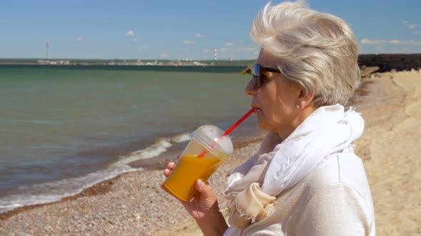 Thumbnail for Senior Woman Drinking Shake on Summer Beach