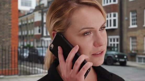 Charming young blonde lady in her 30s talking with someone on smartphone outside
