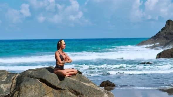 Thumbnail for Pretty Blond Girl in Black Top Relaxes in Yoga Pose Lotus on Purple Mat Against Ocean Waves Running