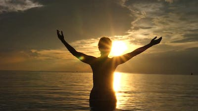 Motivational Uplifting Concept. Woman With Arms Raised At Sunset On The Beach In The Sea.