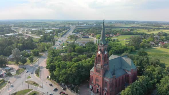 Thumbnail for Church in Small City Among Pastures. Drone Footage. Red Church Is Roman Catholic Church.