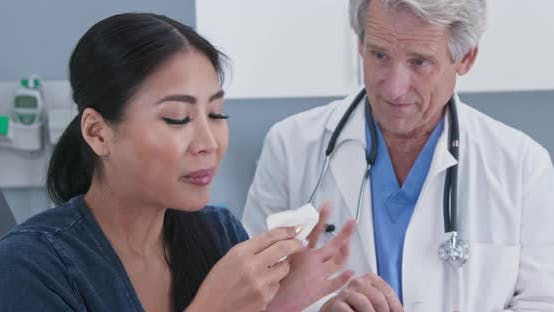 Thumbnail for Sick woman has the flu or cold symptoms and blows her nose while visiting clinic