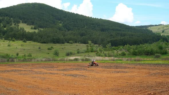 Thumbnail for Farmer Seeding Field with Tractor in Green Countryside of Balkans