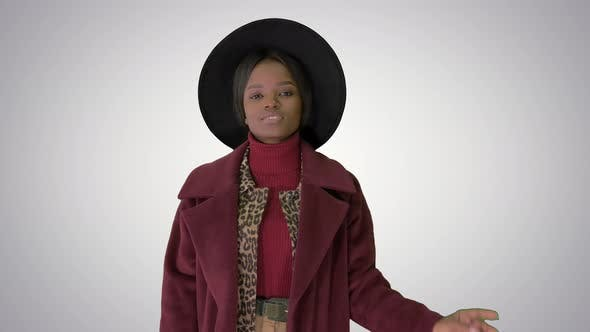 Thumbnail for Cute Afro Model in Coat Touching Hat Walking on Gradient Background.