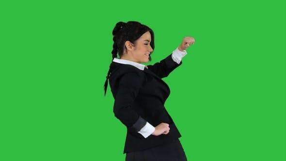 Adorable confident young business woman dancing on a Green