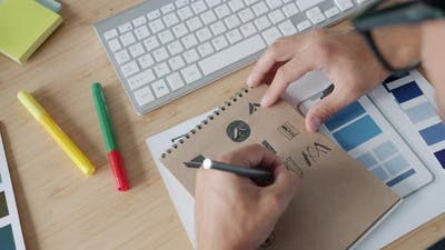 Closeup of Designer's Hand Drawing Logos in Notepad Working at Desk in Office