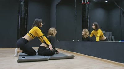 Female Trainer in Yellow Sportswear is Stretching Young Woman in Black Sportswear