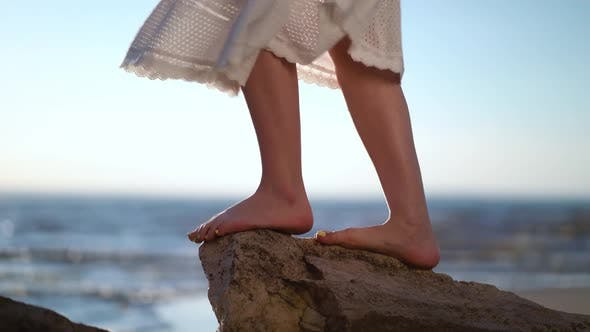 Female Feet Standing on a Stone on the Bech.